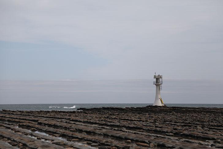 青島の裏側。鬼の洗濯板と灯台のコントラスト
